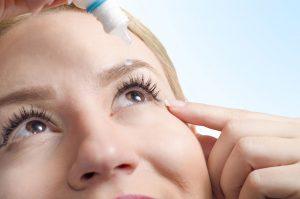 Photo of woman putting eye drops in her eye