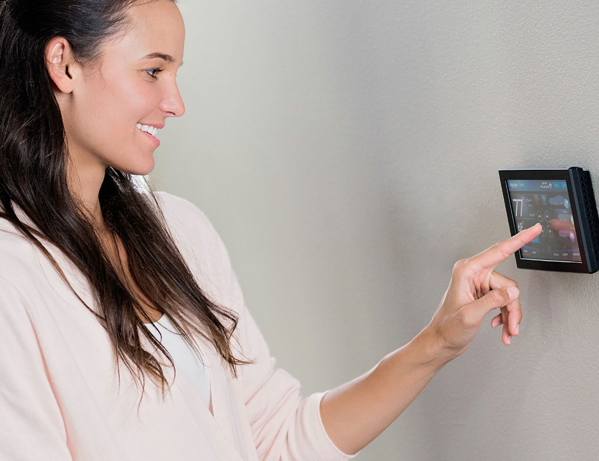 Woman using Aprilaire thermostat